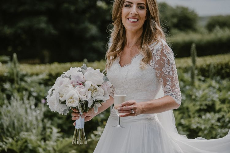 Beautiful Bride in a Lace Bodice and 3/4 Sleeve Naomi Neoh Wedding Dress Holding her Pink and White Peony Bouquet