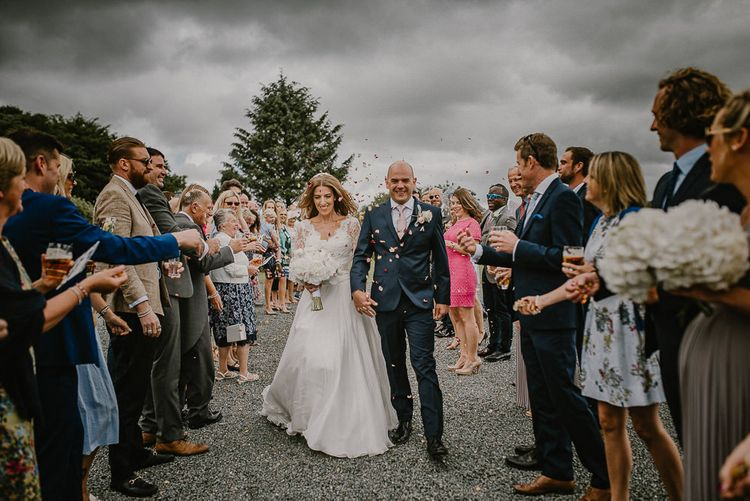 Confetti Moment with Bride in Naomi Neoh Wedding Dress and Groom in Navy Blue Ted Baker Suit