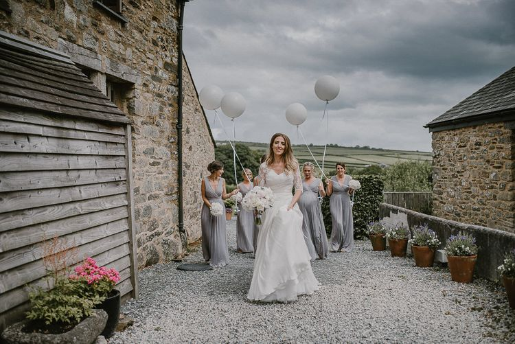 Bride in Naomi Neoh Wedding Dress and Lace Jacket with Her Bridesmaids Following Holding Giant Balloons