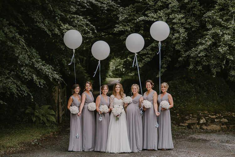 Bridal Party with Bride in Naomi Neoh Dress and Bridesmaids in Grey TFNC Dresses holding Giant White Balloons