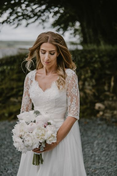 Classic Bride in Naomi Neoh Wedding Dres with Lace Jacket Holding a Pink and White Peony Wedding Bouquet