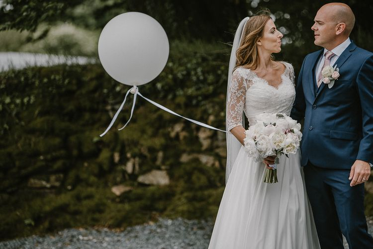 Bride in Naomi Neoh Wedding Dress and Groom in Blue Ted Baker Suit Holding a Giant Balloon on a String