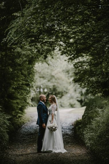 Bride in Naomi Neoh Wedding Dress and Groom in Blue Ted Baker Suit in a Country Lane