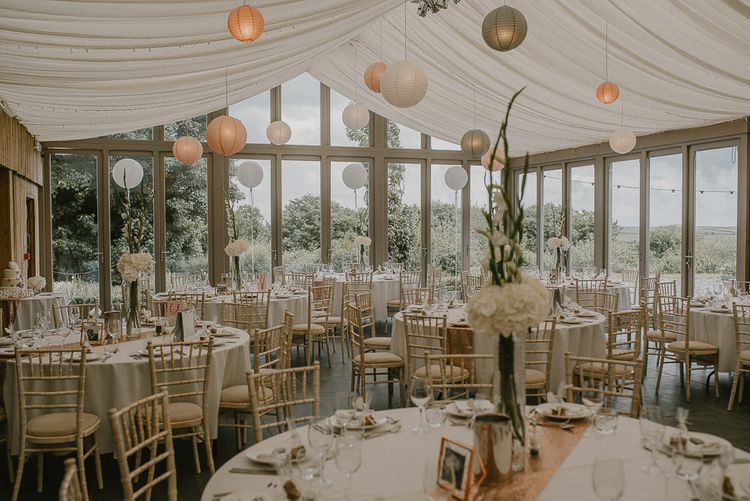 Glasshouse Wedding Reception with Drapes and Hanging Paper Lanterns