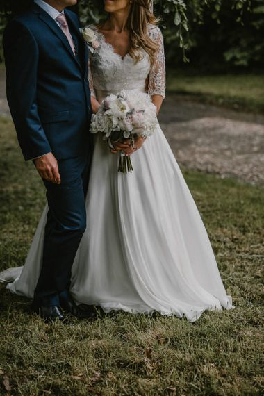 Bride in Naomi Neoh Wedding Dress Holding a Peony Bouquet with Her Groom in a Blue Ted Baker Suit