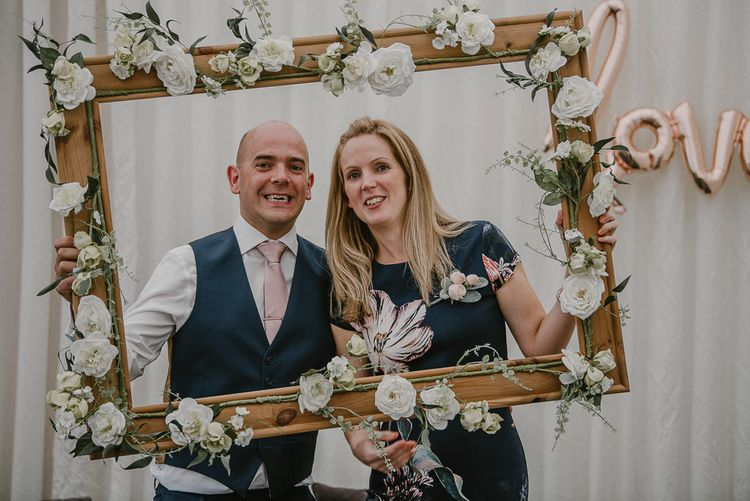 DIY Wooden Frame Covered in Faux Flowers as Photo Booth Prop