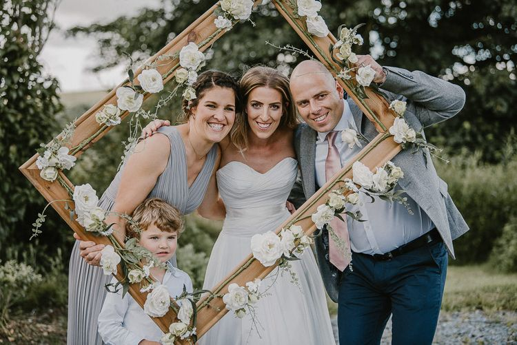 Bride and Wedding Guests Holding the DIY Wooden Frame Covered in Faux Flowers as Photo Booth Prop