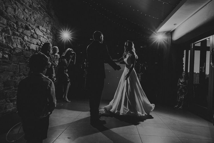 Black and White Portrait of The Bride and Groom Enjoying Their First Wedding Dance