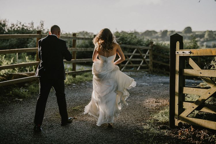 Golden Hour Portrait with Bride and Groom Walking Down a Country Lane