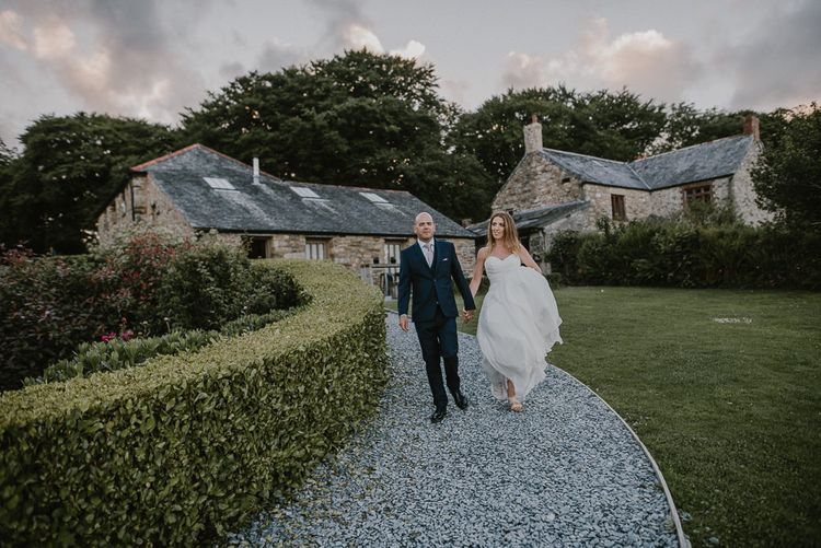 Bride and Groom Walking Down the Country Land with Trevenna Barn Wedding Venue as Their Backdrop