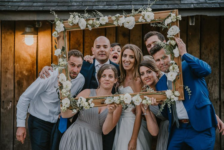 Wedding Guests Posing in the DIY Wooden Frame Covered in Faux Flowers as Photo Booth Prop