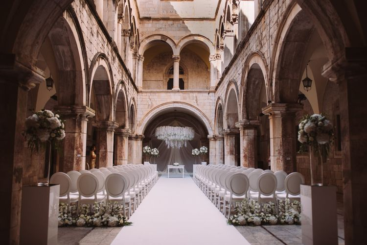 Wedding Ceremony in a 16th-century palace with White Chairs and Flowers