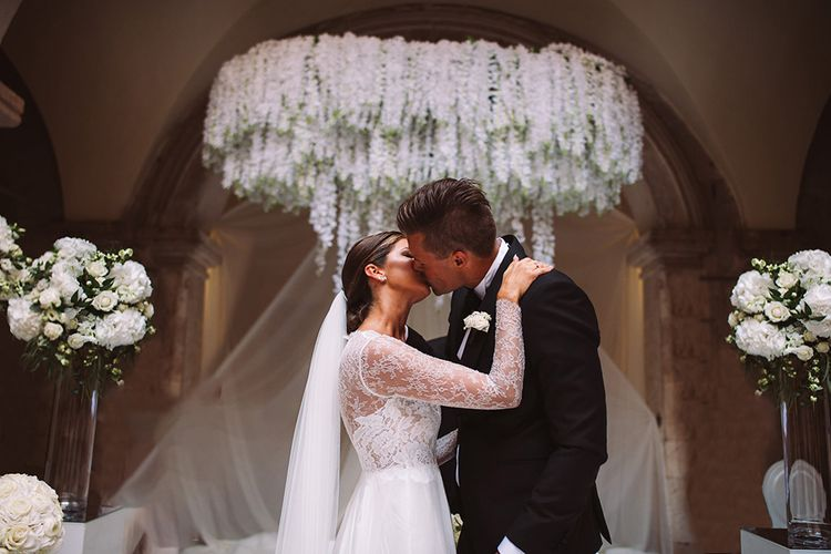 Bride and Groom Just Married Kissing at The Altar with Floral Chandelier Backdrop
