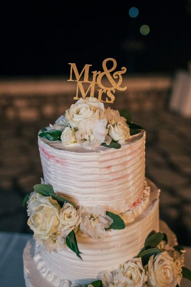Gold Mr & Mrs Cake Topper on Elegant Wedding Cake with Frosting and Flowers