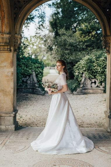 Bride Standing in a Courtyard Holding a Bouquet