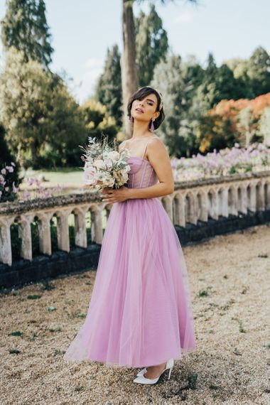 Beautiful Bride in Blush Wedding Dress Holding a Bouquet in White Stiletto Shoes