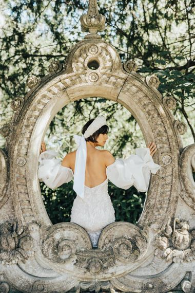 Bride in Strapless Wedding Dress Wearing an Ornate Headdress Tied with Ribbon