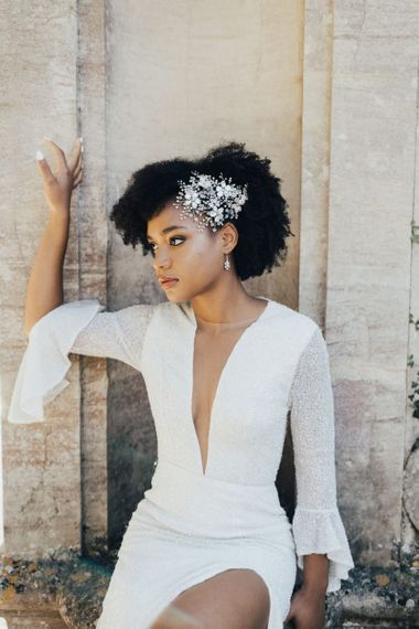 Black Bride with Afro Hair Wearing an Ornate Pearl Hair Accessory and Shimmering Emma Beaumont Wedding Dress