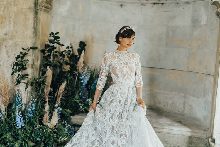 Beautiful Bride in Lace Emma Beaumont Wedding Dress with High Neck and Long Sleeves Wearing a Pearl Wedding Hair Accessory