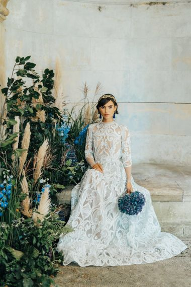 Bride in Lace Wedding Dress Holding a Blue Hydrangea Bouquet