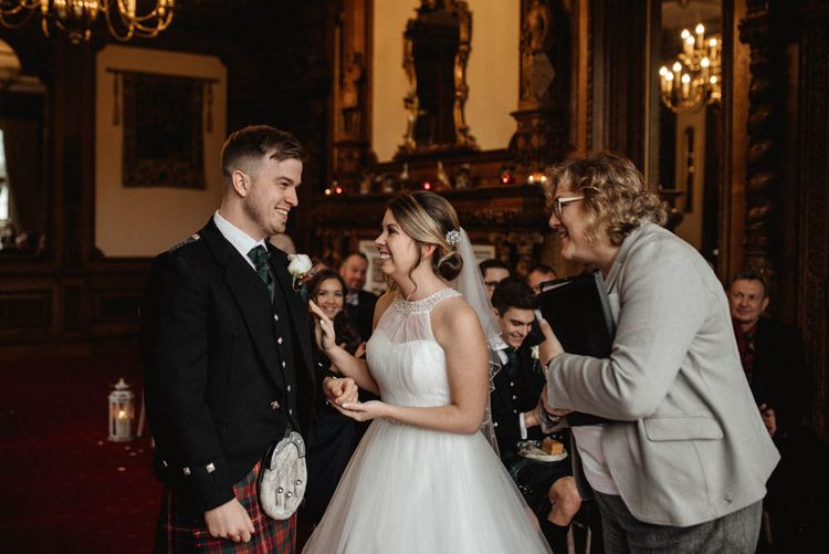 Bride in Halterneck Wedding Dress and Groom in Tartan Kilt Laughing at Wedding Ceremony