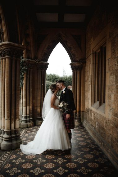 Bride in Halterneck Wedding Dress and Groom in Tartan Kilt Kissing on the Grounds of Manor by The Lake Wedding Venue