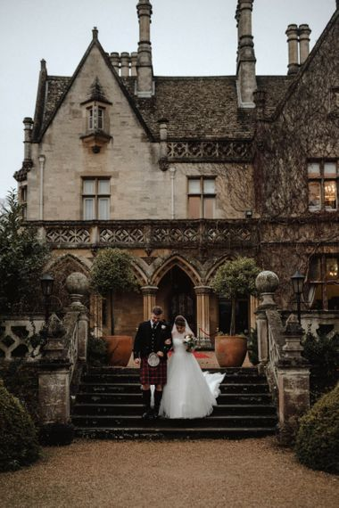 Bride in Halterneck Wedding Dress and Groom in Tartan Kilt on the Grounds of Manor by The Lake Wedding Venue