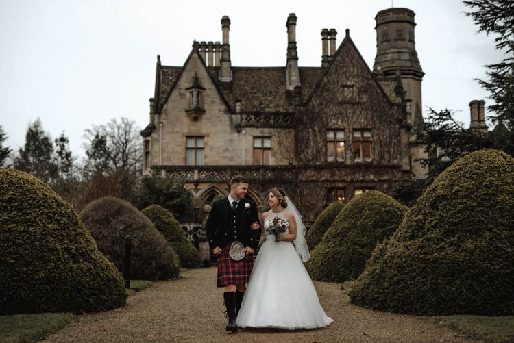 Bride in Halterneck Wedding Dress and Groom in Tartan Kilt Arm in Arm