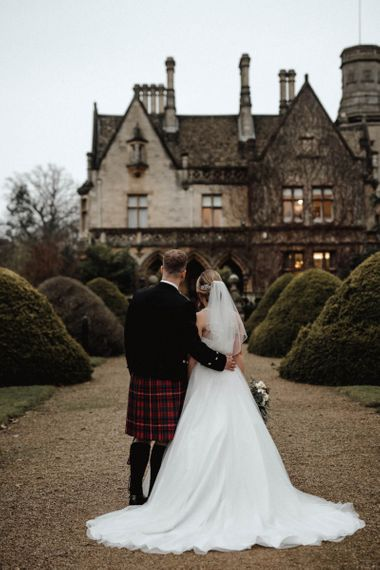 Bride in Halterneck Wedding Dress and Groom in Tartan Kilt Embracing