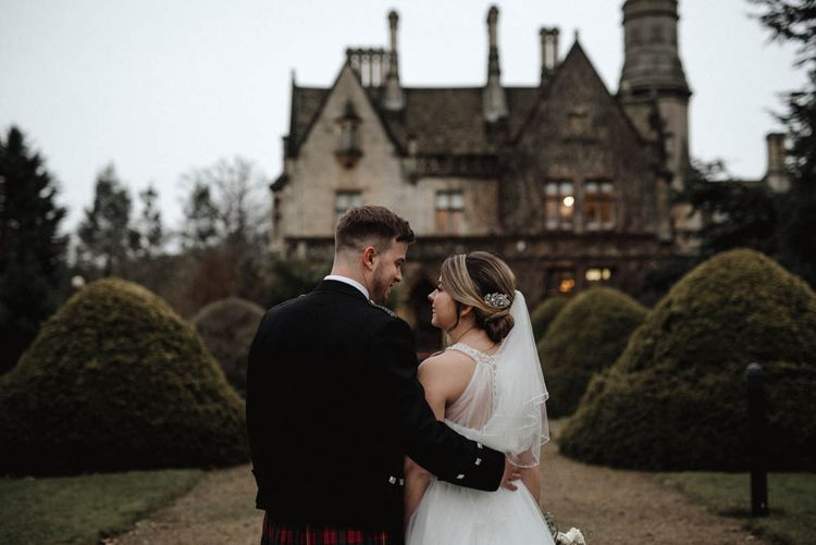 Bride in Halterneck Wedding Dress and Groom in Tartan Kilt Cuddling