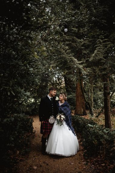 Bride Wrapped in Tartan Throw and Groom in Tartan Kilt Walking on the Grounds of Manor by The Lake Wedding Venue
