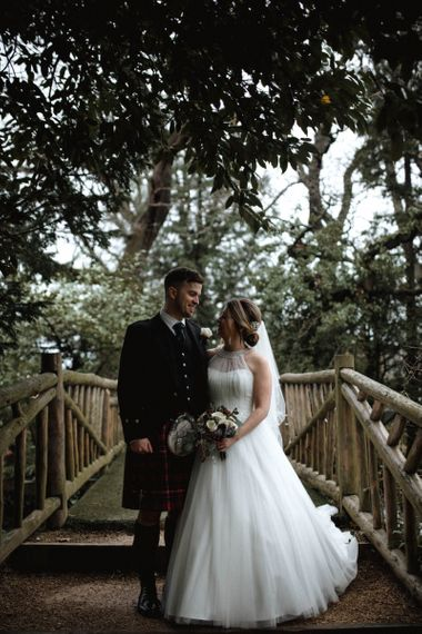 Bride in Halterneck Wedding Dress and Groom in Tartan Kilt Standing on a Bridge