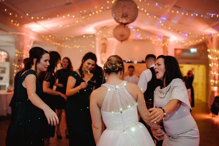 Evening Reception Dance Floor Action with Bride in Halterneck Wedding Dress and Chic Chignon  Bridal Hairstyle