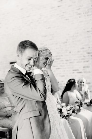 Bride in Lace Pronovias Wedding Dress and Groom in Navy Suit Laughing During the Wedding Ceremony