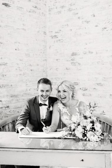 Bride in Lace Pronovias Wedding Dress and Groom in Navy Suit Signing the Register