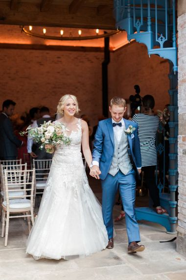 Bride in Lace Pronovias Wedding Dress and Groom in Navy Suit Holding Hands Exiting the Wedding Ceremony