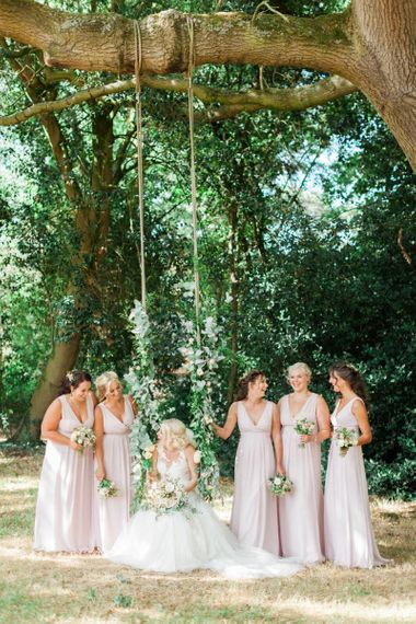 Bridal Party Portrait with Bride in Pronovias Wedding Dress Sitting on a Swing and Bridesmaids in Pink Maids to Measure Dresses