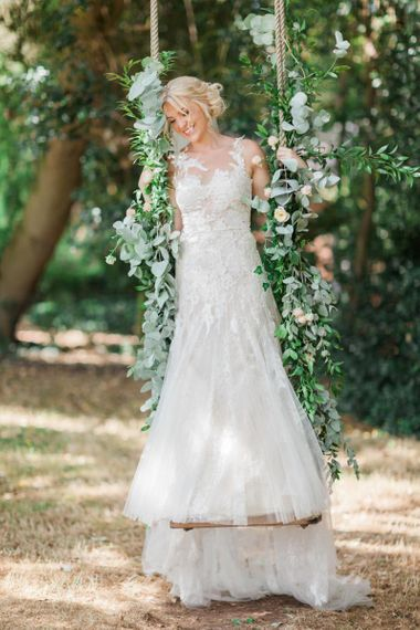 Bride in Lace and Tulle Pronovias Wedding Dress Standing on a Swing Covered in Ivy