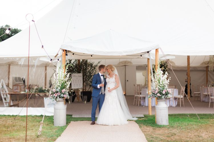 Bride in Pronovias Wedding Dress and Groom i Navy Suit Standing in Front of Their Sperry Tent Marquee Reception