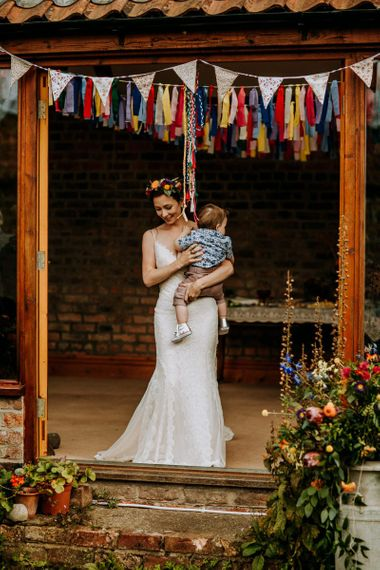 Bride in Lace Sottero & Midgley Wedding Dress Holding Her Infant