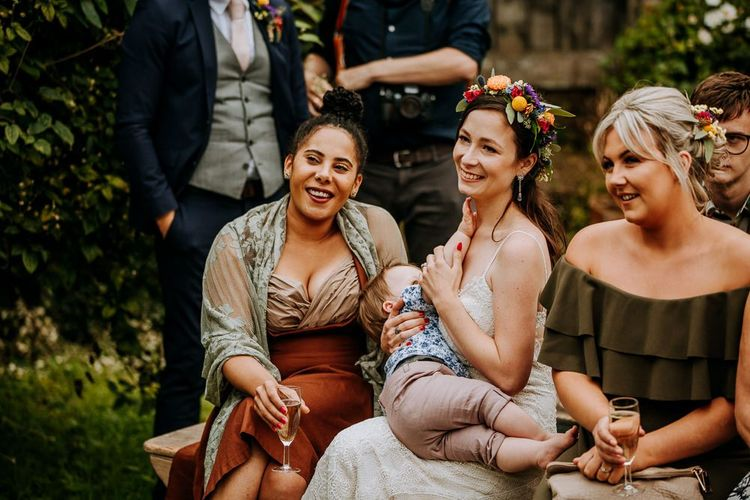 Bride Wearing a Colourful Flower Crown Sitting with Her Wedding Guests