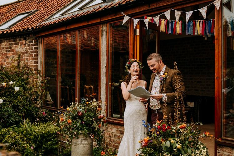 Bride in Sottero & Midgley Wedding Dress and Colourful Flower Crown and Groom in Brown Wool Suit and Floral Shirt Laughing