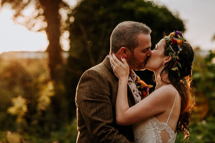 Bride in Sottero & Midgley Wedding Dress and Colourful Flower Crown and Groom in Brown Wool Suit and Floral Shirt