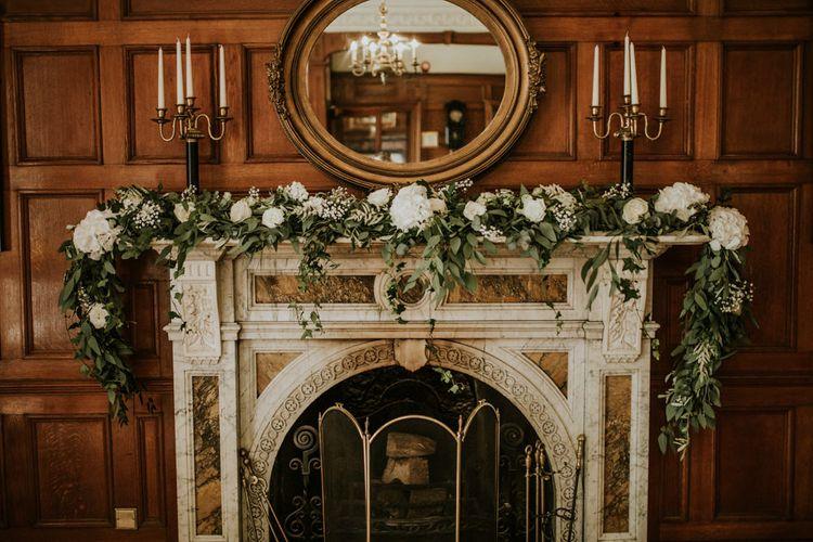 Greenery & White Fireplace Garland Wedding Flowers | Green, White & Gold Wedding at Buckland Tout Saints, Devon |  Darina Stoda Photography