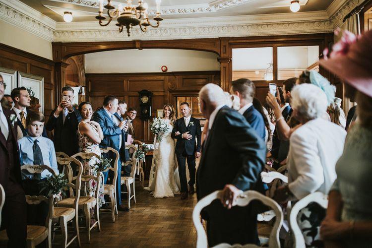 Wedding Ceremony | Bridal Entrance in Pronovias Oringo Lace Bridal Gown & Cape | Green, White & Gold Wedding at Buckland Tout Saints, Devon |  Darina Stoda Photography