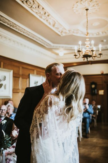 Wedding Ceremony | Bride in Pronovias Oringo Lace Bridal Gown & Cape | Groom in Blue Marks and Spencer Suit | Green, White & Gold Wedding at Buckland Tout Saints, Devon |  Darina Stoda Photography