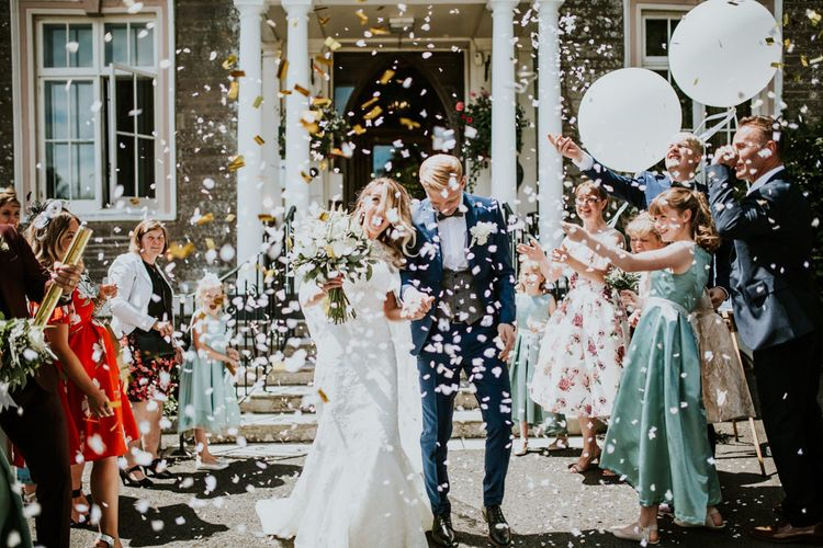 Confetti Moment | Bride in Pronovias Oringo Lace Bridal Gown & Cape | Groom in Blue Marks and Spencer Suit | Green, White & Gold Wedding at Buckland Tout Saints, Devon |  Darina Stoda Photography