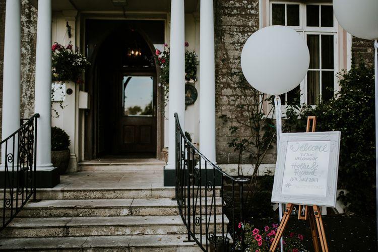 Welcome Wedding Sign & Giant Balloon | Green, White & Gold Wedding at Buckland Tout Saints, Devon |  Darina Stoda Photography