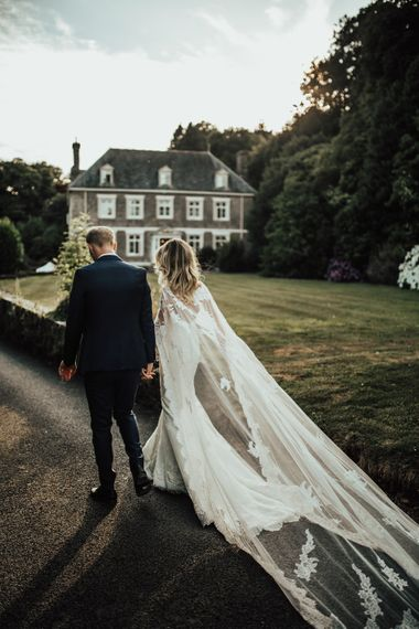 Bride in Pronovias Oringo Lace Bridal Gown & Cape | Groom in Blue Marks and Spencer Suit | Green, White & Gold Wedding at Buckland Tout Saints, Devon |  Darina Stoda Photography