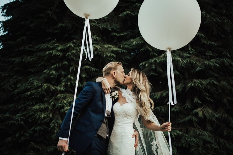 Giant Balloons | Bride in Pronovias Oringo Lace Bridal Gown & Cape | Groom in Blue Marks and Spencer Suit | Green, White & Gold Wedding at Buckland Tout Saints, Devon |  Darina Stoda Photography